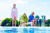 Happy kids warm up in towels after swimming — Stock Photo