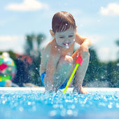 Cute boy having fun, playing near the pool — Stock Photo