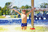 Excited boy enjoying summer under the water flow — Stock Photo