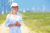 Young female researcher analyzes readouts on wind power station — Stock Photo