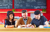Happy friends sitting in cafe, studying — Stock Photo