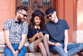 Stylish friends having fun together with the phone — Stock Photo