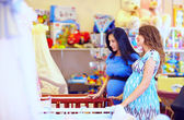 Pregnant women choosing cot for baby — Stock Photo