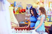 Pregnant women choosing cot for baby — Stok fotoğraf