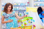 Pregnant woman buying cradle with mobile toy for baby — Stock Photo