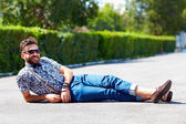 Cheerful young adult man lying on the road — Stock Photo