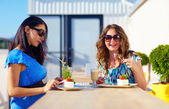 Happy female friends enjoying cakes in cafe, pregnant women — Stock Photo
