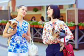 Happy women talking on crowded city street — Stock Photo