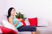 Pregnant woman watching tv at home — Stock Photo