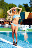 Sexy blonde girl posing near the pool — Stock Photo