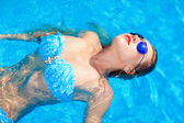 Young girl relaxing in summer pool — Stock Photo