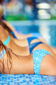 Row of seductive female bodies in pool — Stock Photo