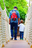 Father and son travelling by suspension bridge — Stock Photo