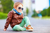 Cute stylish boy in leather jacket sitting on the road — Stock Photo