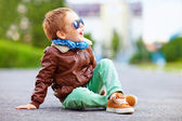 Happy boy in leather jacket posing on the ground — Stock Photo