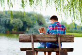 Father and son sitting on the bench near the lake — Stockfoto