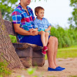 Father and son sitting on the bench under willow tree — Stock Photo #51034525