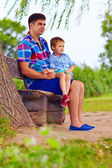 Father and son sitting on the bench under willow tree — Stock Photo
