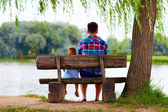 Father and son sitting on the bench near the lake — Stock Photo