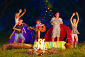 Kids having fun around campfire. focus on fire — Stock Photo