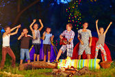 Happy kids dancing around campfire — Stock Photo