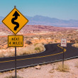 Road signs on a twisty road of Nevada desert and mountains — Stock Photo