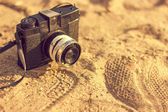 Retro camera on sand — Stock Photo