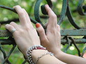 Young girl's hands, resting on an old rusted gate — Stock Photo