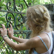 Stock Photo: Young girl resting her hands on old rusted gate