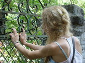 Young girl resting her hands on an old rusted gate — Stock Photo