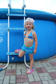 A little girl in a bathing suit in a large inflatable pool — Stockfoto