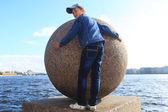 Garçon étreindre boule de granit sur la Neva à Saint-Pétersbourg — Photo