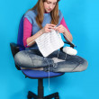 Stock Photo: Womknits, sitting on office chair