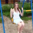 Smiling girl swinging on a swing — Stock Photo