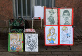 Sale cartoons street artist at the Palace Square. St. Petersburg, Russia. — Stock Photo