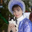 Stock Photo: Cat in hands of Snow Maiden on background of Christmas tree