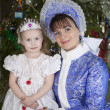 Stock Photo: Maiden and little girl with Christmas tree