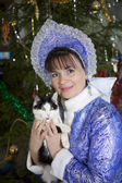 Cat in the hands of the Snow Maiden on a background of the Christmas tree — Stock Photo