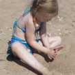 Girl playing with sand on beach — Stock Photo #27614353