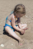Girl playing with sand on the beach — Stockfoto