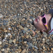 Girl backfilled pebbles on the beach — Stock Photo