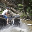 A quad bike along the bed of a mountain river — Stock Photo