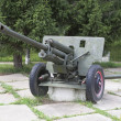 Artillery gun ZIS-3 in square near monument to fallen soldiers in World War II village Syamzha, Vologdregion, Russia — Stock Photo #31019989