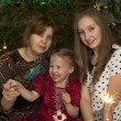 Portrait of womwith two daughters in Christmas tree — Stock Photo #38110685