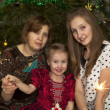 Family at Christmas tree background with sparklers — 图库照片