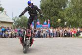 Alexei Kalinin rides standing on a motorbike  Moto show in Verkhovazhye, Vologda region, Russia — Stock Photo