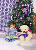 Boy and bear reading a book under the Christmas tree — Stock Photo