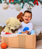 Laughing baby in the box with a bear in a Christmas setting — Foto de Stock