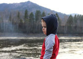 Boy by the river in the mountains — Stock Photo