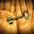 Key in the hands of an elderly person — Stock Photo